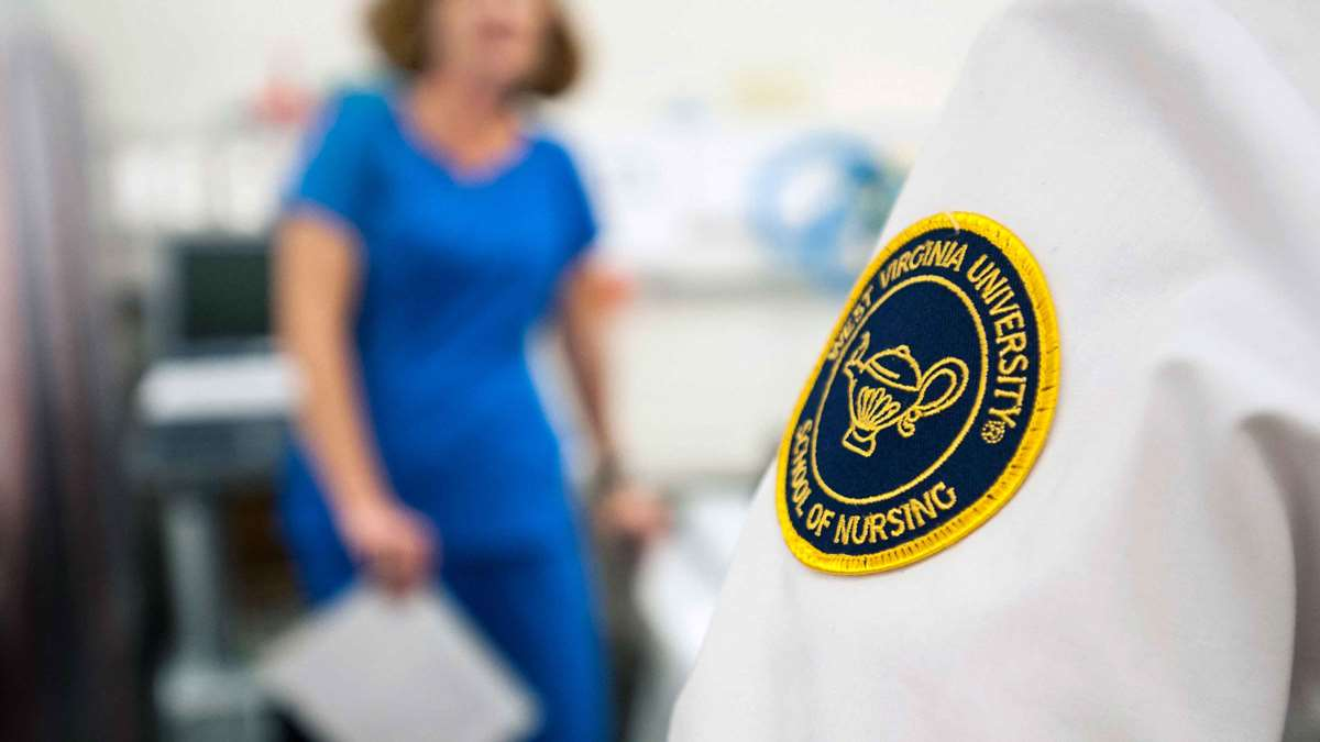 A photo of a nurse's sleeve with the School of Nursing patch in the foreground, in front of an out-of-focus nurse standing in the background