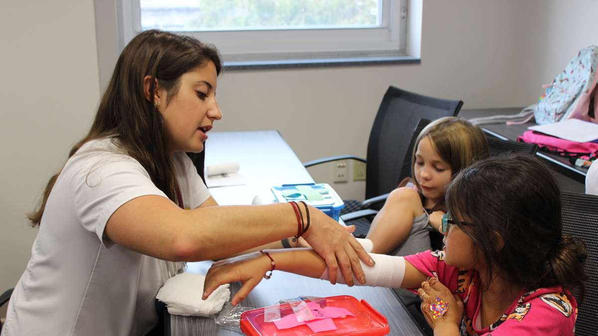 Nursing student shows girl scouts how to wrap an arm.